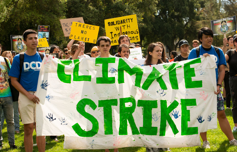 """Climate strikers hold banner, """"Climate Strike,"""" green letters."""