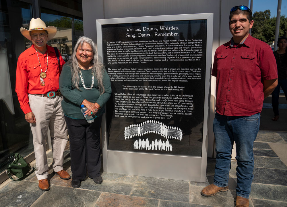 Three people pose with historical marker.