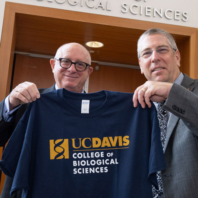 Two men holding College of Biological Sciences T-shirt.