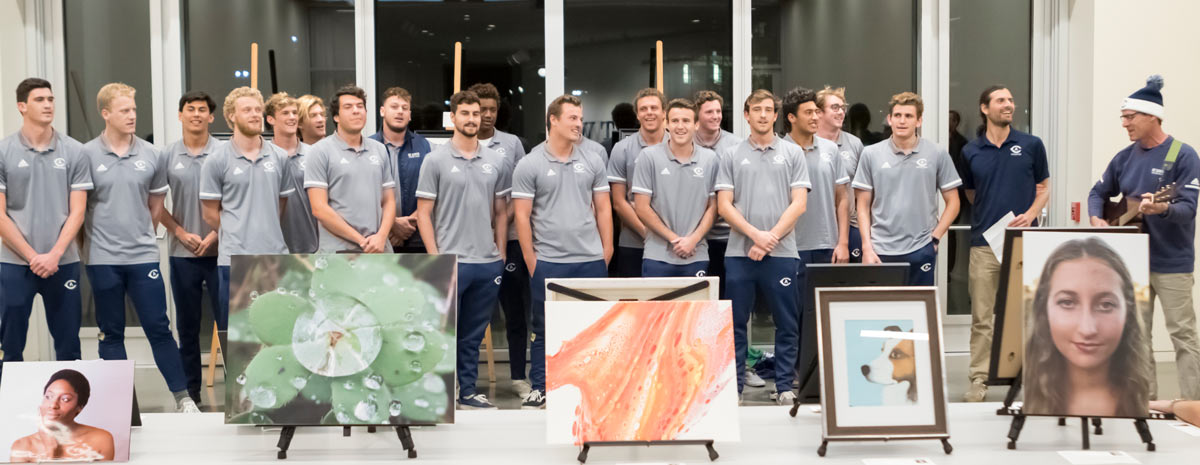 Men's water polo team, assembled as a chrous, singing.