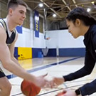 Basketball players talk and dribble with each other.