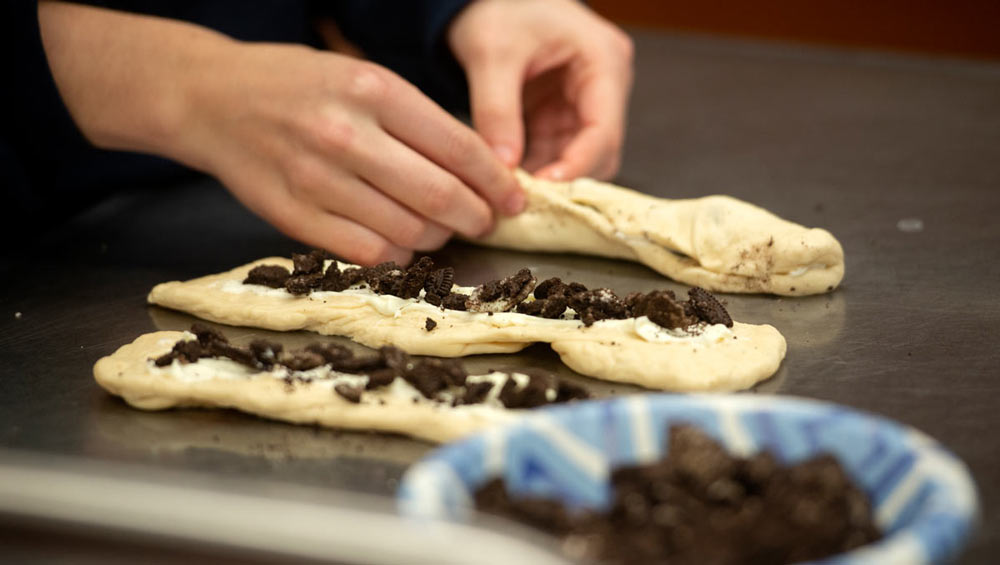 Hands add pieces of Oreo cookies to challah dough.