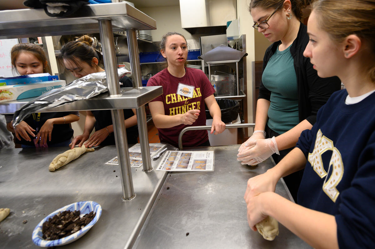 Female student gives instructions to other student volunteers in kitchen.