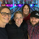 Four people pose for a selfie at a bowling alley.