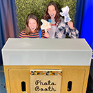 Two people pose for a photo in a photo booth.