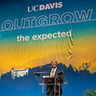 "Chancellor Gary S. May stands on stage in front of banner reading ""Outgrow the Expected"""