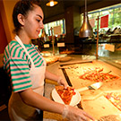 A student worker serves pizza at the CoHo.