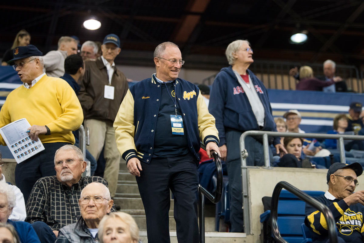 Ralph J. Hexter, in Aggie jacket, walks down basketball bleachers.