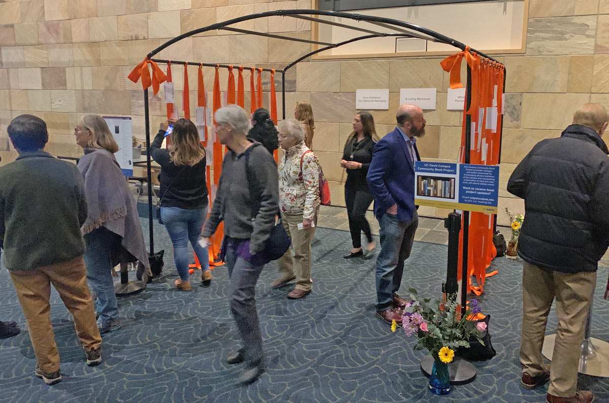 orange ribbons with tags attached, hanging from metal structure, with a dozen people viewing.