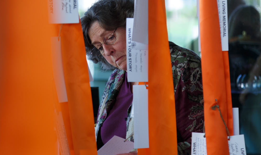 Woman reads tags on orange ribbons.