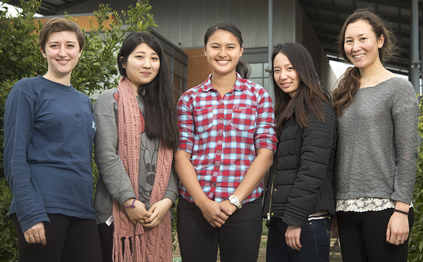 Five college women stand in garden in front of two-story orange building.
