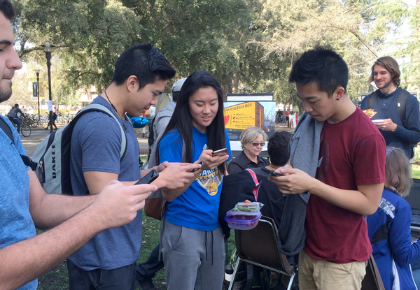 Students on mobile devices, on the Quad