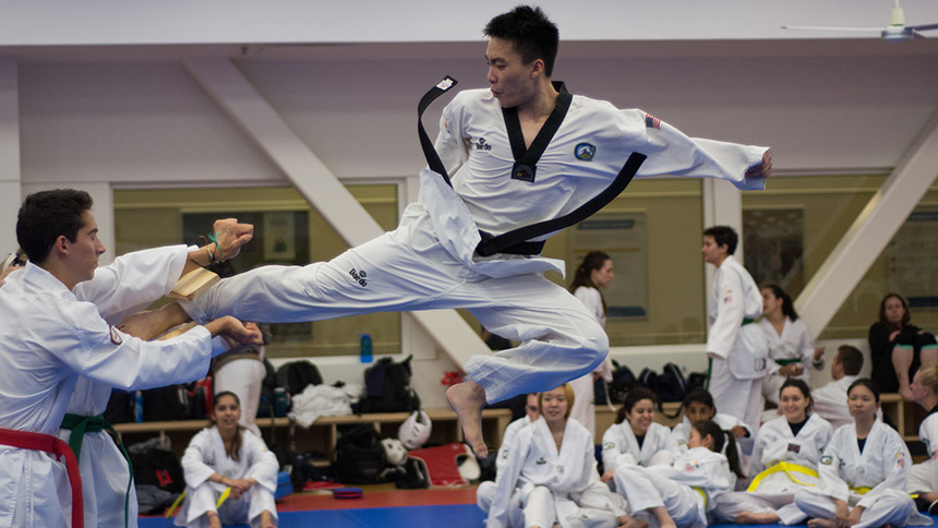 Taekwondo club member leaping in the air with a kick