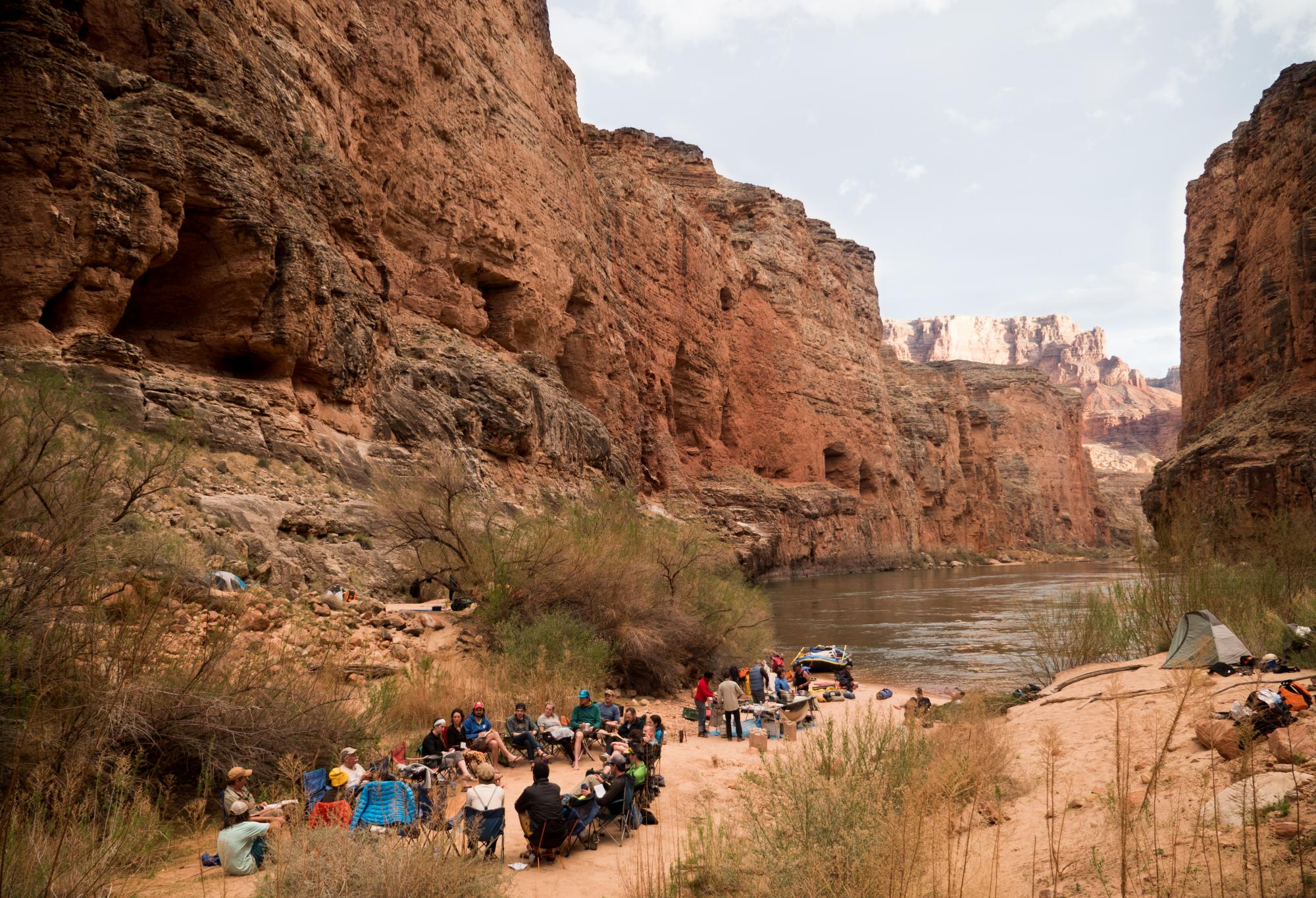 Men and women sit in circle on beach by Colorado River in Grand Canyon