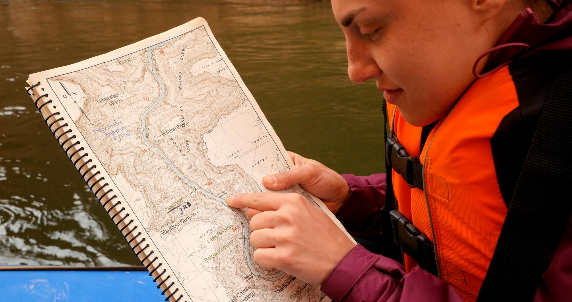 Woman looks at map of Colorado River while on a river raft