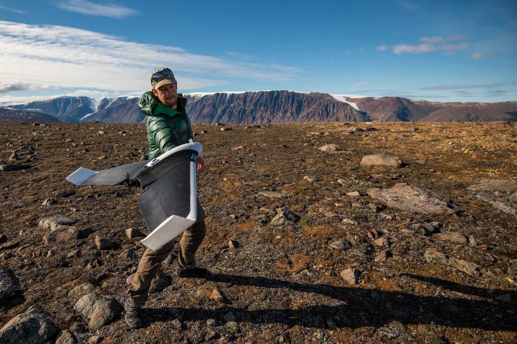male scientist flies drone in arctic landscape