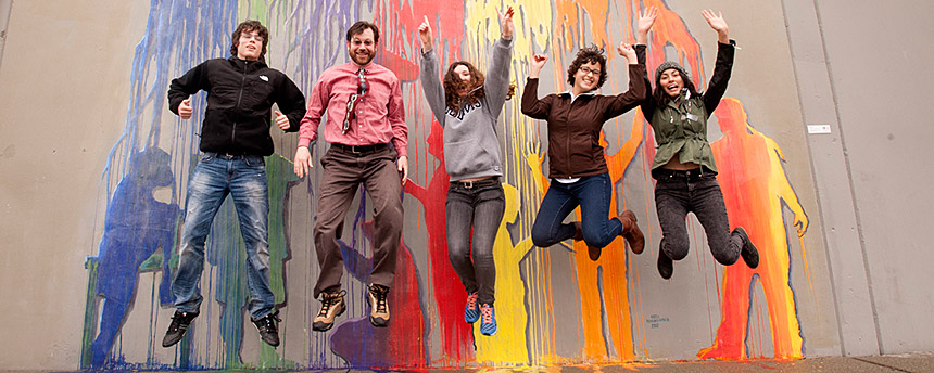 A group of students jumping high with a mural of paint dribbles behind them