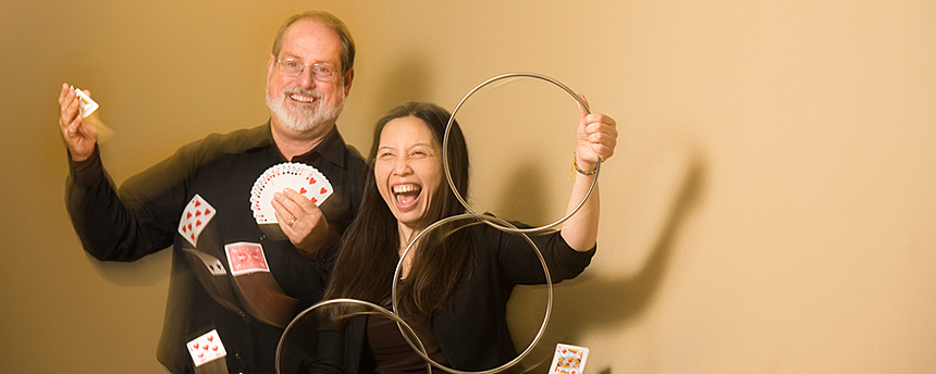 A man with cards flying in the air and a woman with three magic rings, both having a lot of fun