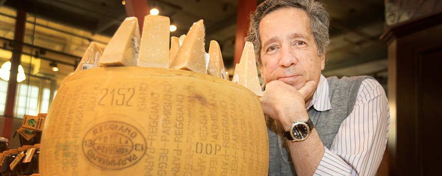 Man looking at the camera behind a big block of parmesan cheese.