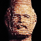 a brick chimney constructed in the likeness of Robert Arneson