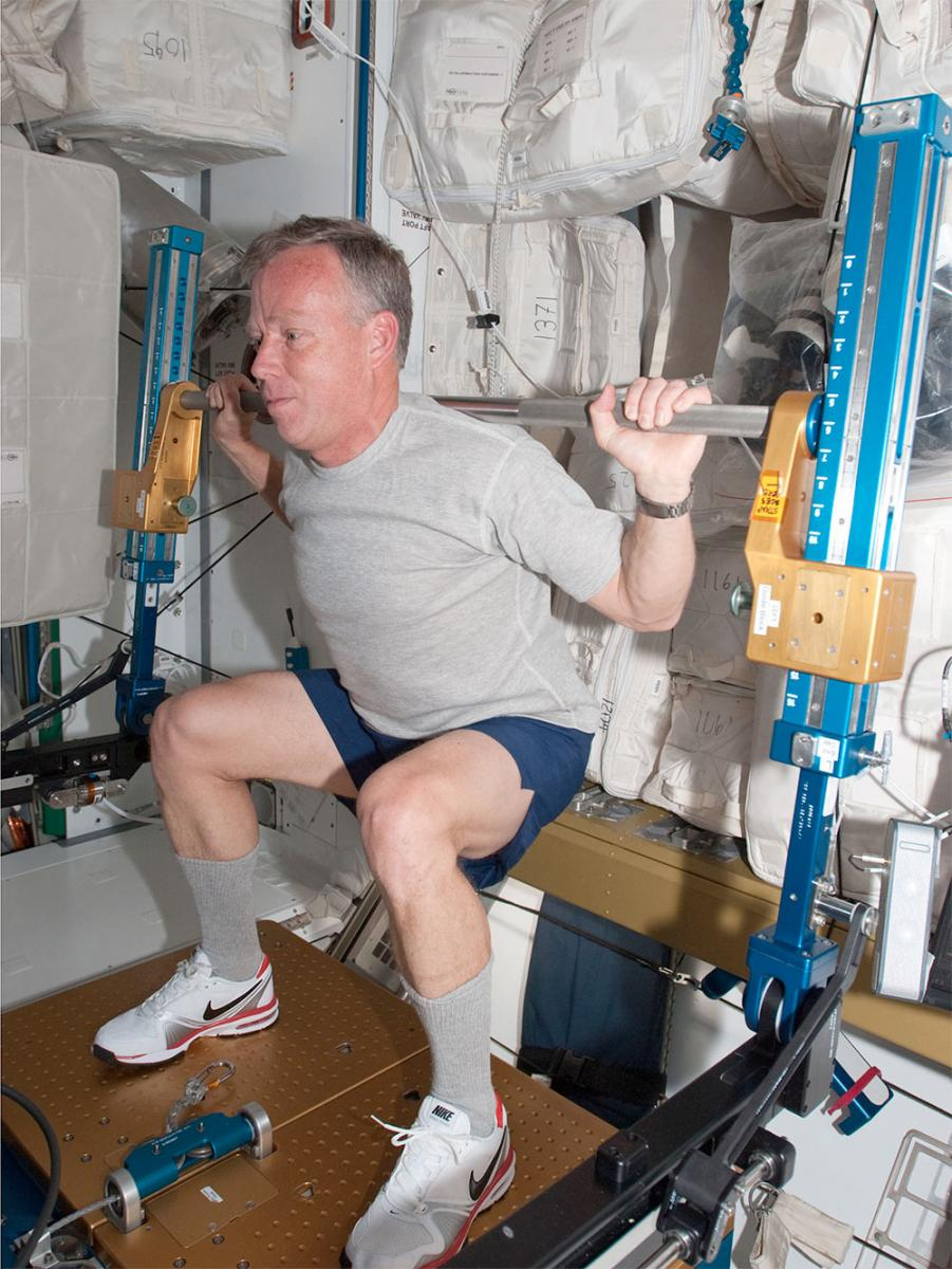 NASA astronaut Steve Lindsey, STS-133 commander, exercises using the advanced Resistive Exercise Device (aRED) in the Tranquility node of the International Space Station while space shuttle Discovery remains docked with the station.