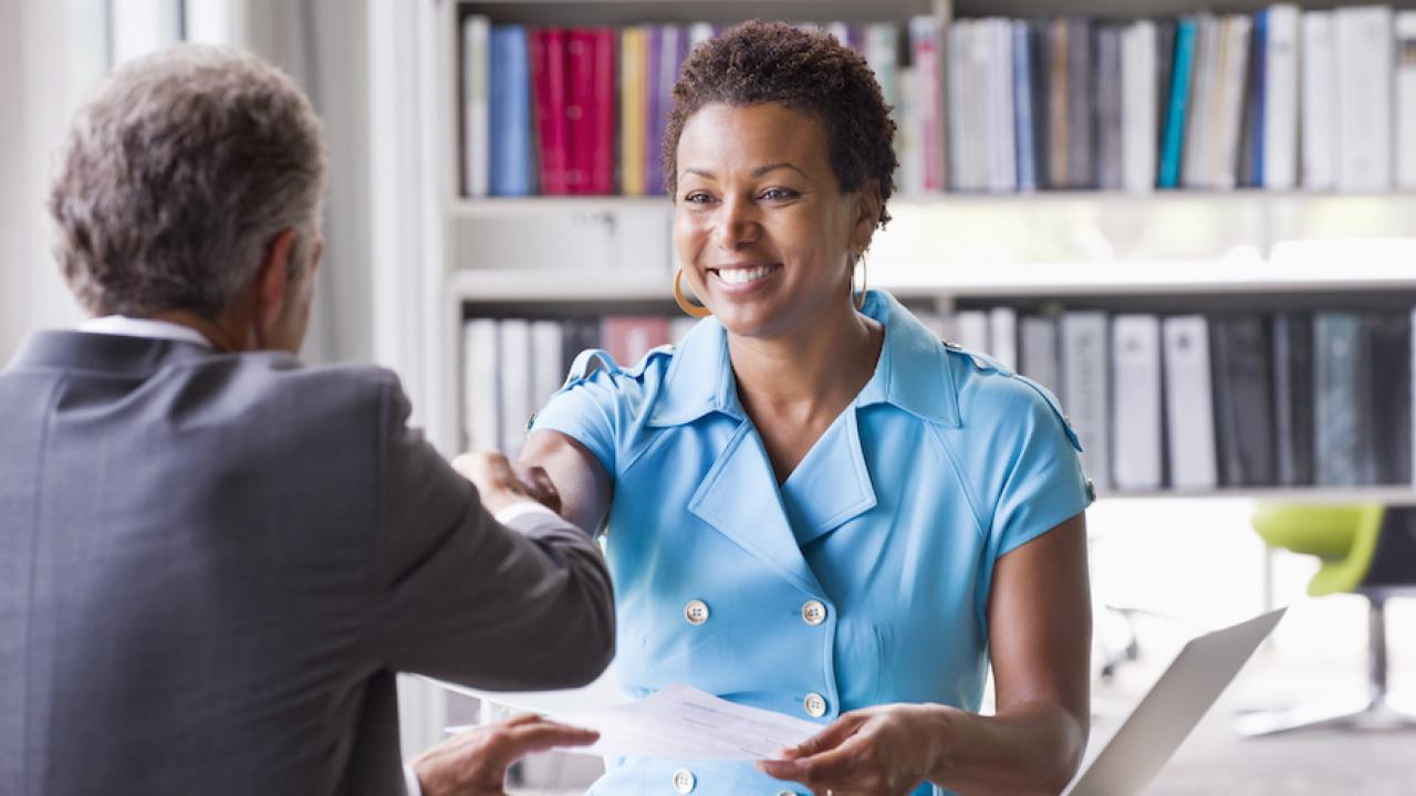 Six must-have skills career HR, a woman shakes hands at a job interview.