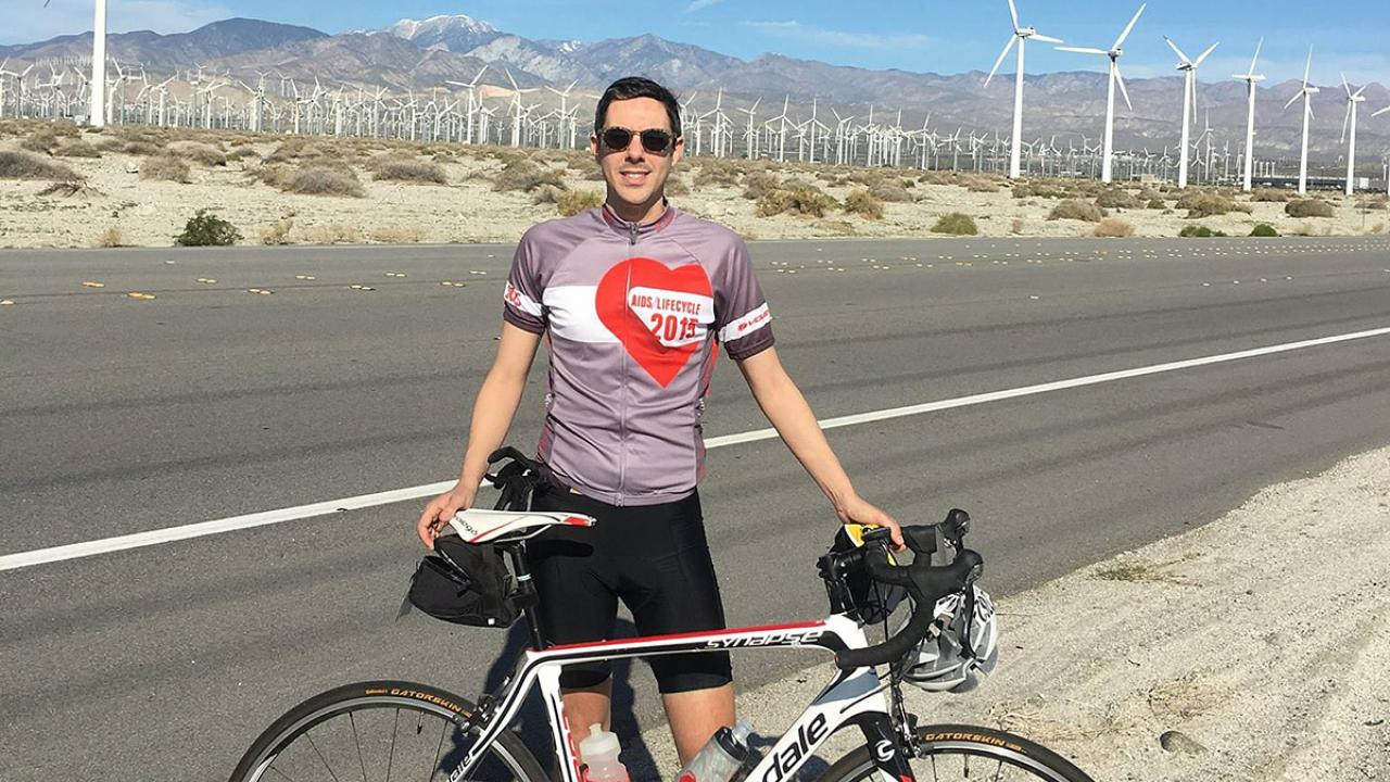 International relations graduate Tim Mizrahi poses with a road bike next to a highway with windmills in the background