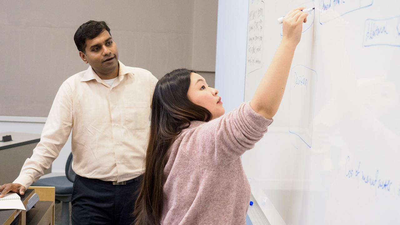 Business school student YiYi Han (foreground) at the white board writing while an instructor watches from behind.