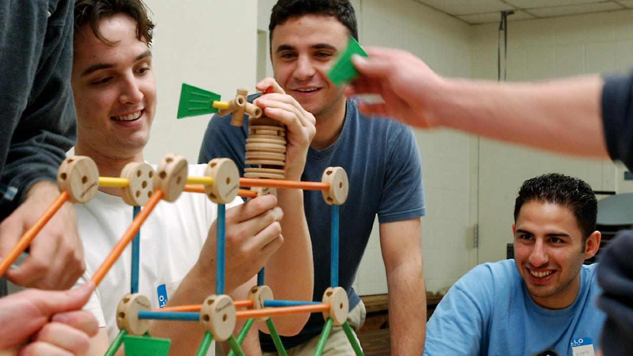 A team of male students using Tinketoys to build a structure