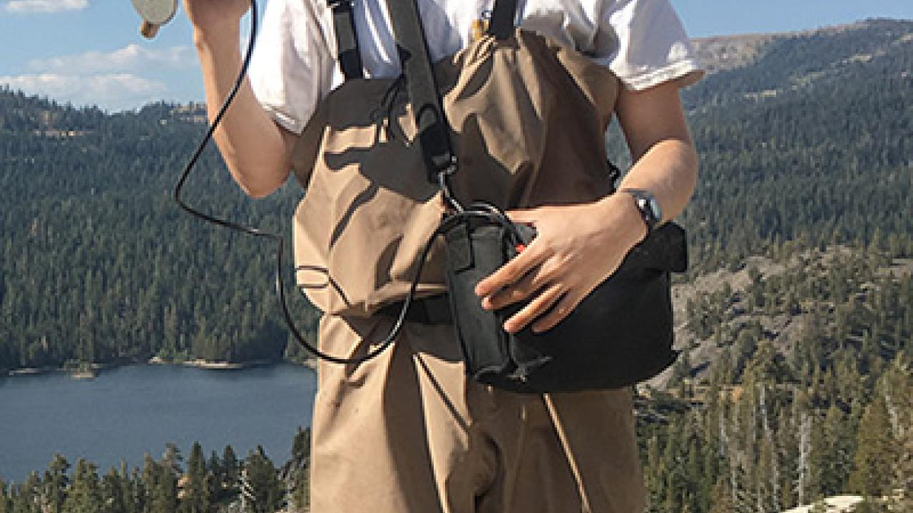Jake Trusheim with monitoring gear and in water-proof overalls in the high Sierra Nevada.