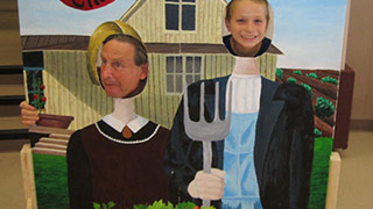Man and boy stick their heads through a cut-out board with the American Gothic as the theme