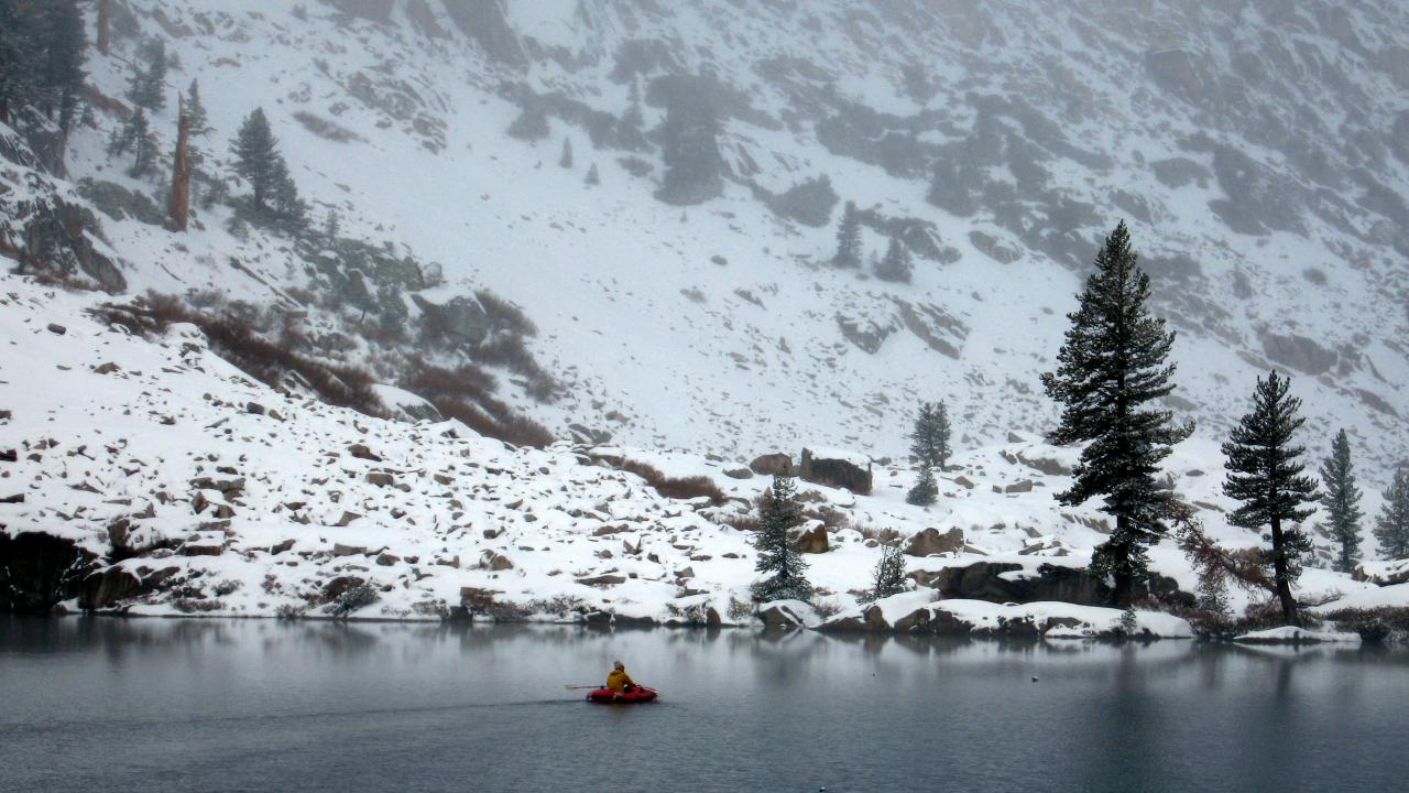 Scientist in boat on Emerald Lake during winter