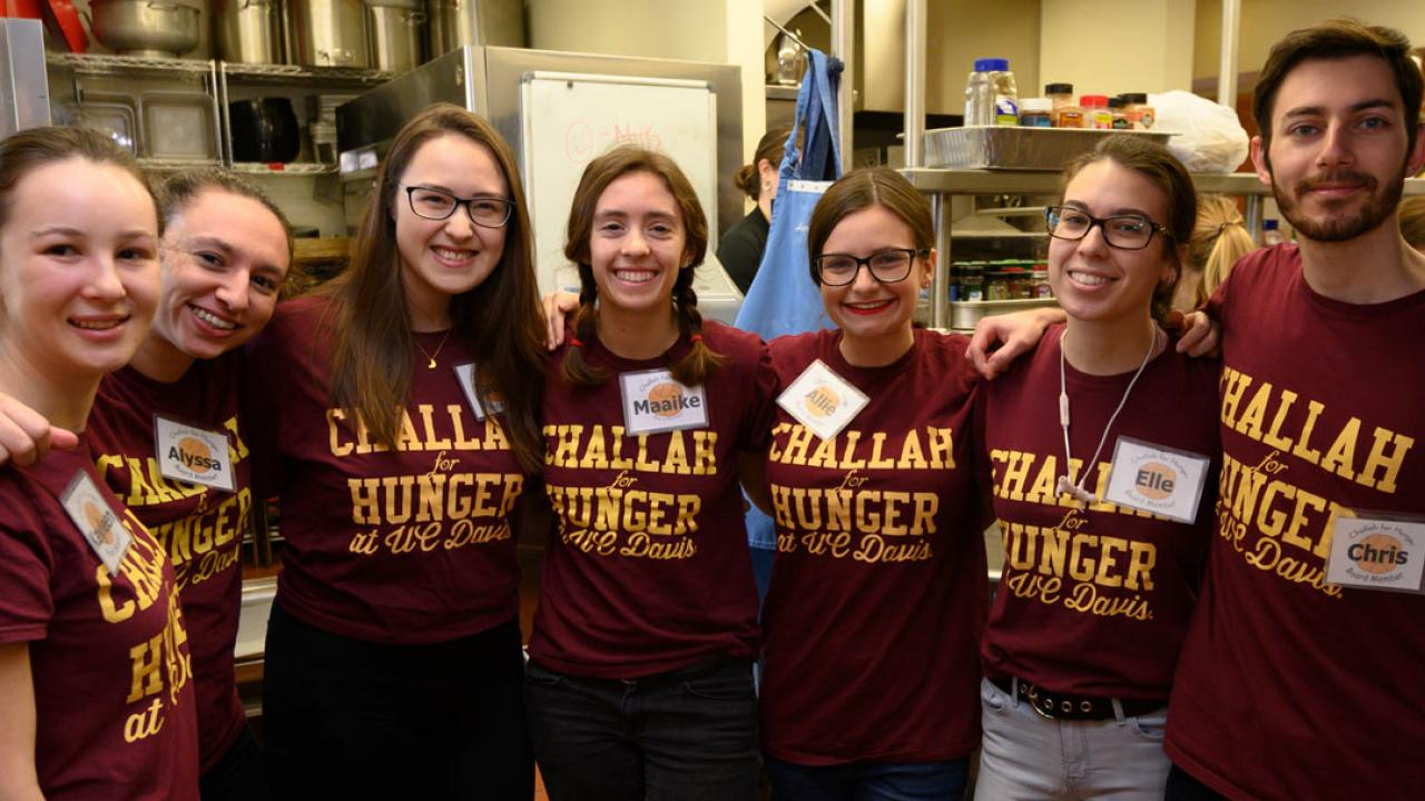 "Students pose in a line in kitchen, all wearing burgundy T-shirts with ""Challah for Hunger UC Davis"" in gold."