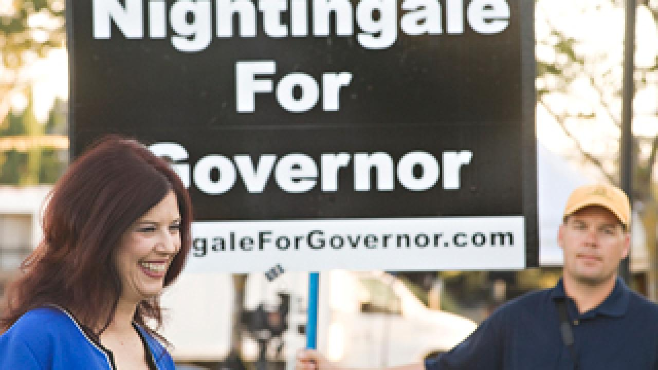 "woman in front of sign ""Nightingale for Governor"" with man holding sign"