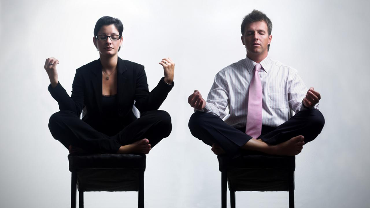 Photo: Employees meditate in chairs at work.
