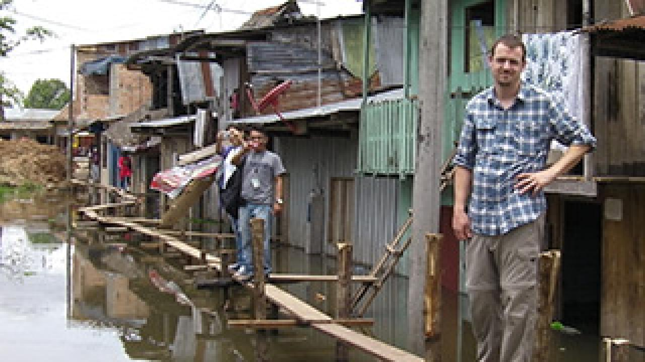 People standing on boards over a river with shacks behind them
