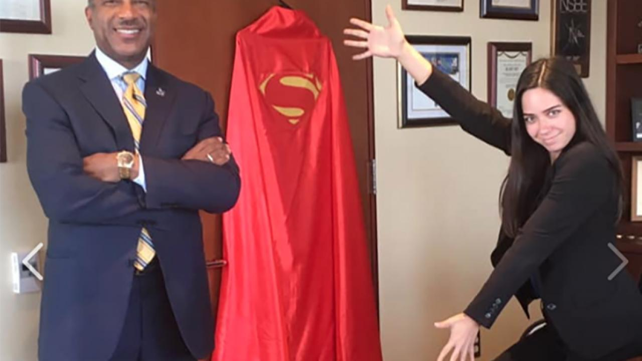 Chancellor Gary S. May and Teddy Cruz beside a hero cape