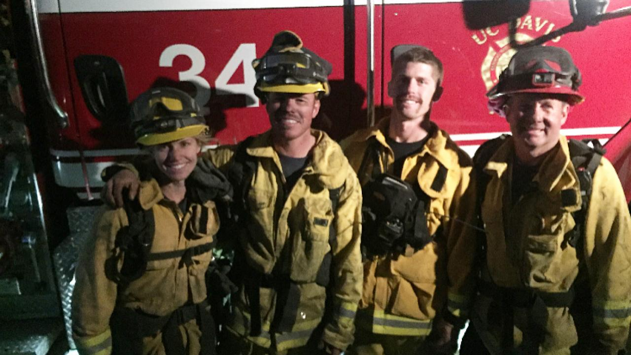 Four firefighters in front of a truck.