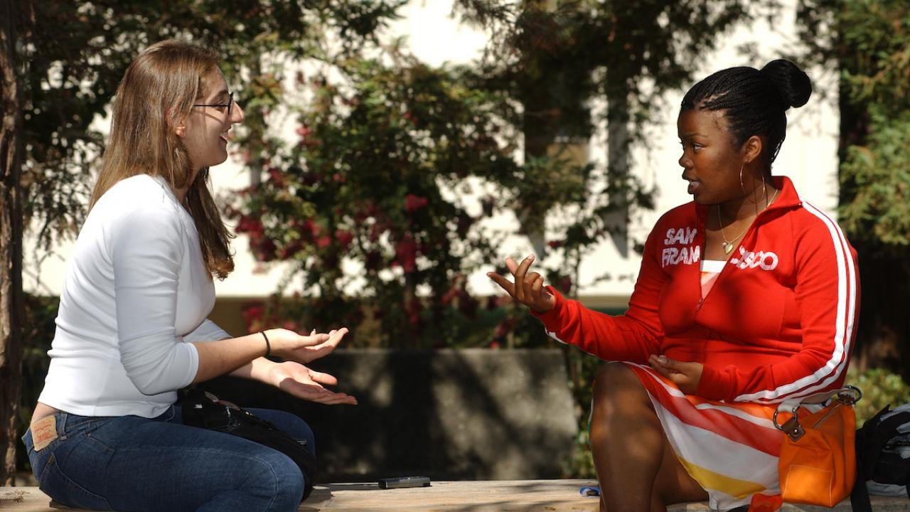 Two female students discuss the classwork outside of Wellman Hall