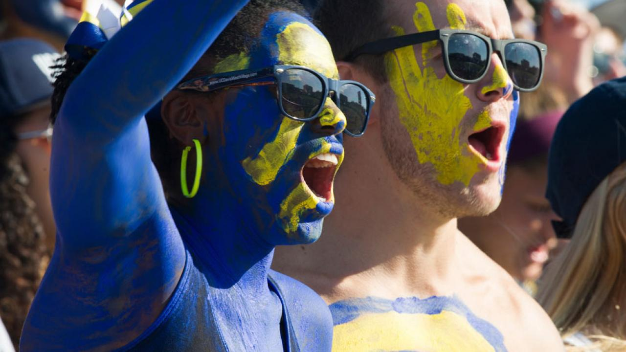 a male and female student painted in UC Davis blue and gold cheer on the Aggies at the annual homecoming football game