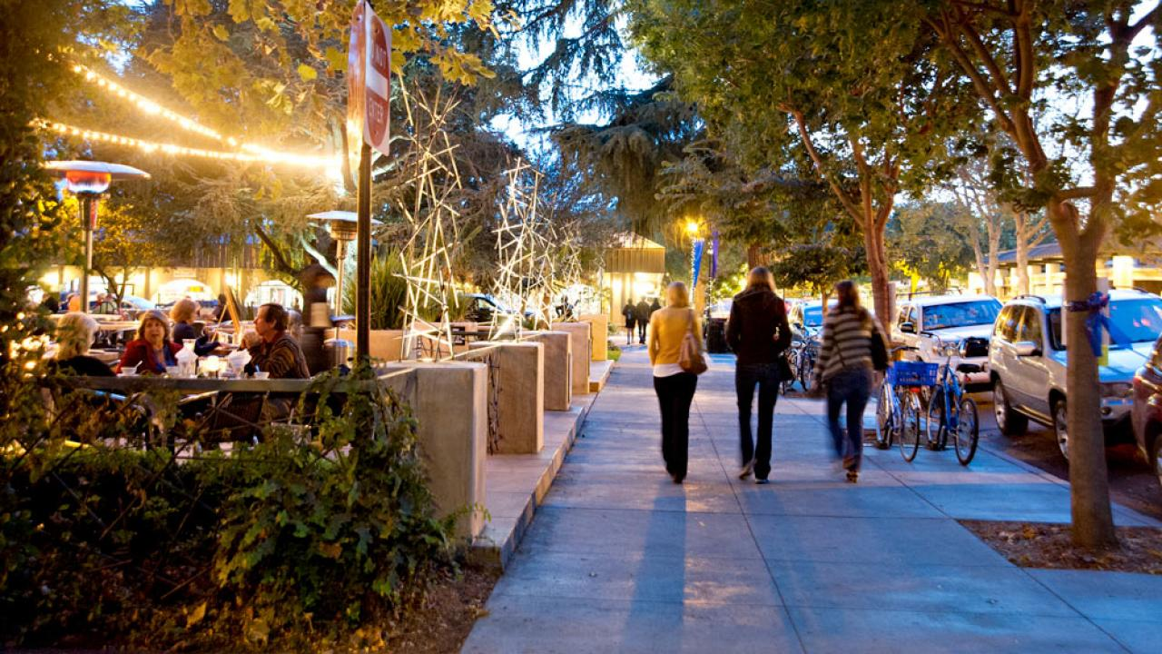 A view of downtown davis during the evening with shoppers and restaurant patrons enjoying the atmosphere