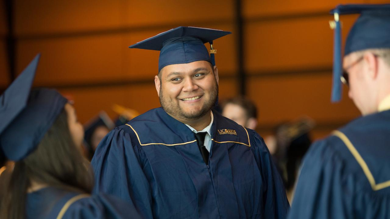 A student smiles among friends in his cap and gown at UC Davis.