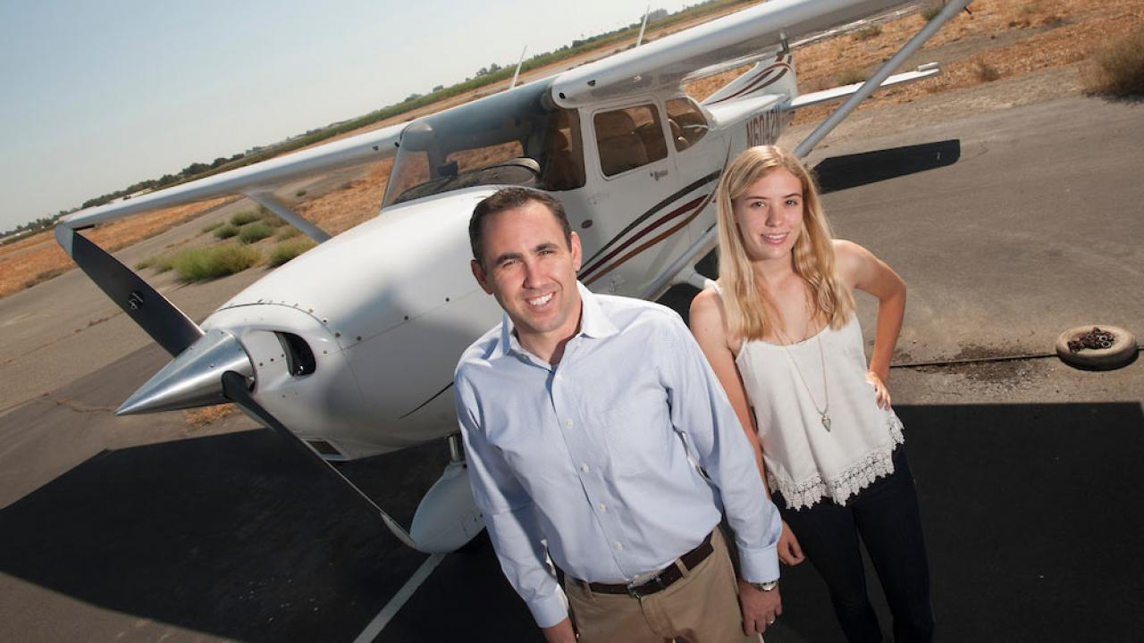 An instructor and student pose for a shot in front of an airplane at UC Davis airport