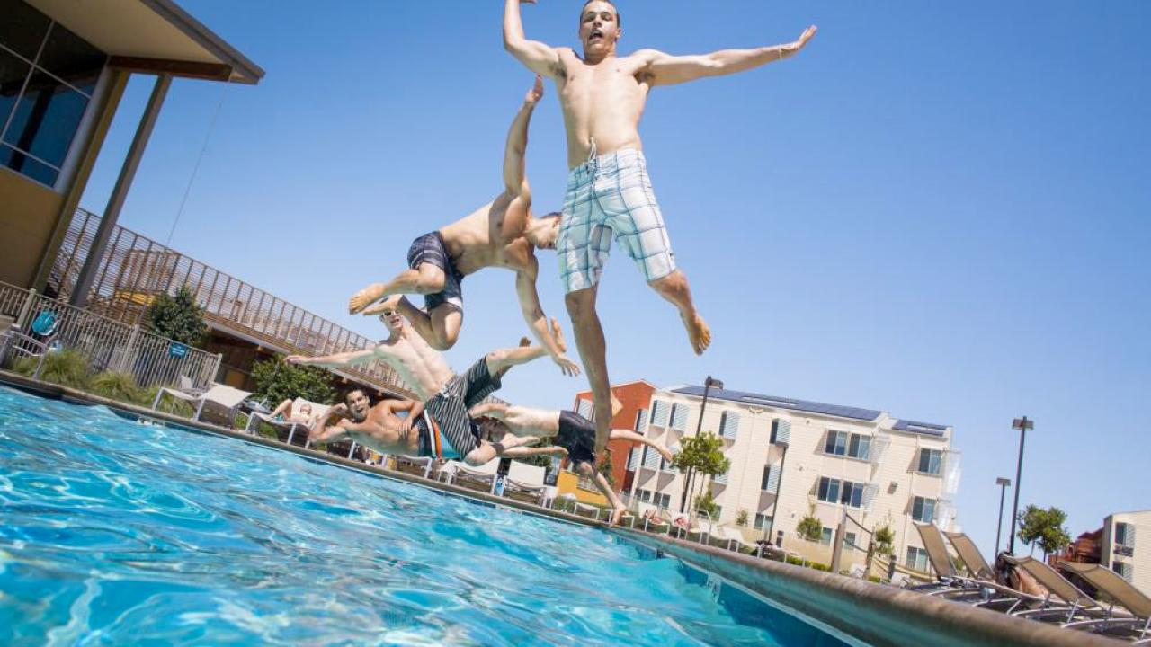 three aggies jumping into the pool at West Village