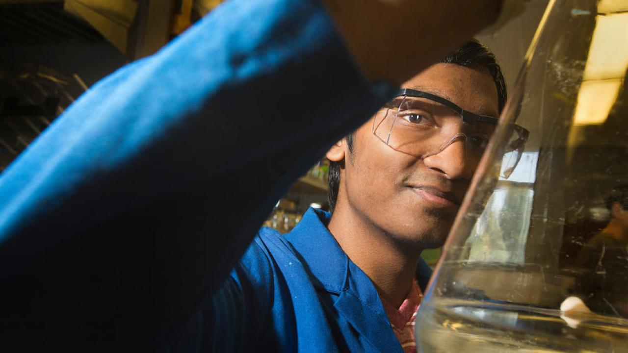 A male student holds up the contents of a lab flask