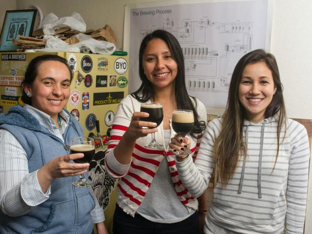 Students raise a glass with their brewing teacher