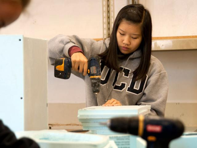 A female student uses a power drill at the craft center