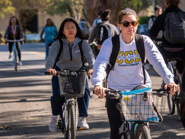 a closeup on two students riding among other students down a road on campus.