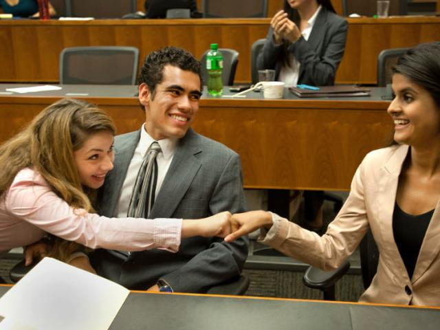 students fist bump after a win at the law school