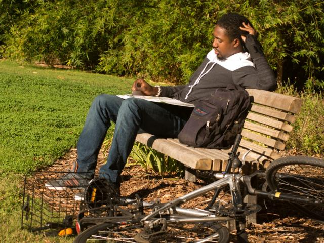a student sitting on a bench and studying in the arboretum